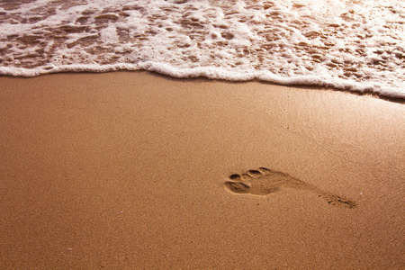 absence: Footprint in the sand on the beach Stock Photo