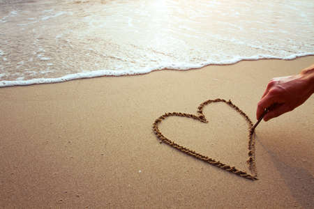 sand writing: heart on the beach, hand drawing on sand