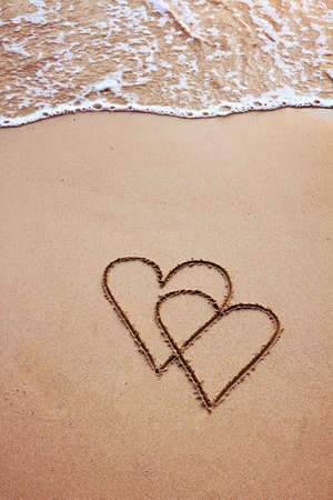 valentine s day beach: couple of hearts drawn in sand, postcard Stock Photo