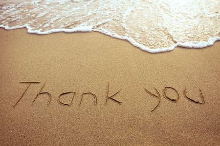 agradecimiento: gracias, palabra dibujado en la playa