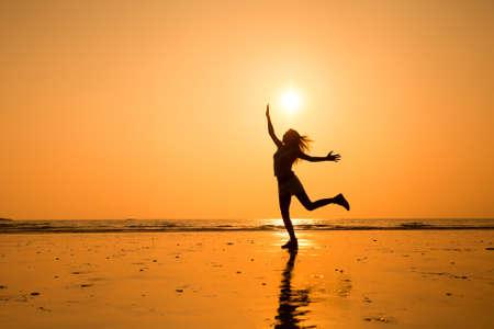 幸せな若い女の子は、健康的な生活をジャンプの抽象的なシルエット