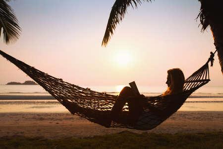 mujer leyendo libro: silueta de la mujer de relax en hamaca en la playa