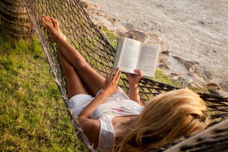 Vrouw liggend in een hangmat op het strand en genieten van een boek lezen