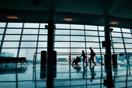 Reisen mit Kindern, Silhouetten der Familie mit Kinderwagen auf dem Flughafen Standard-Bild - 22973020