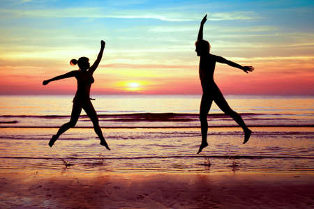 happy couple jumping on the beach, summer vacations photo