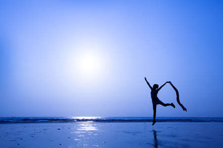 silhouette of woman dancing on the beach photo