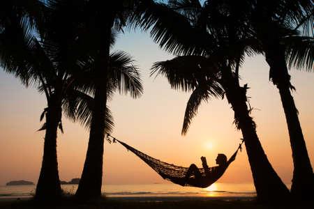 hamaca: silueta de mujer que se relaja en la hamaca con el libro