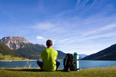 hiking in mountains, young traveller meditate near the lake,  contemplation Banco de Imagens