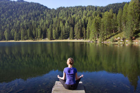 young woman practices yoga near mountain lake photo
