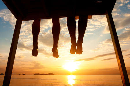 Silhouette der Füße Paare, die auf dem Pier bei Sonnenuntergang am Strand, niedrige Winkel Ansicht sitzen Standard-Bild