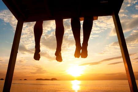 silueta de pies de pares que se sientan en el embarcadero en la playa de la puesta del sol, bajo ángulo de vista