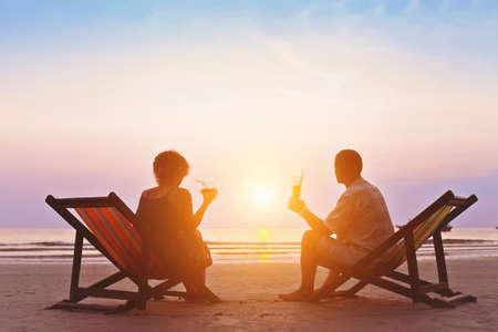 해변에서 낭만적 인 일몰을 즐기는 가족 스톡 콘텐츠