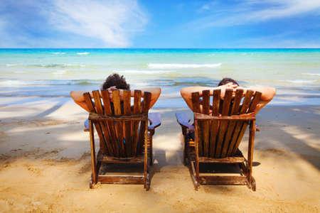 カップルがビーチで休んで