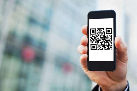 画面上の QR コードにスマート フォンを持っている手 写真素材