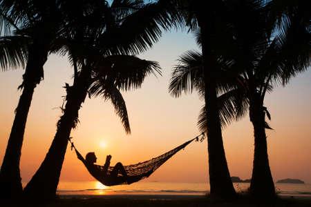 Strandurlaub, Silhouette der Frau in der Hängematte zu lesen