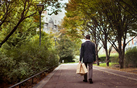 live work city: solitude, lonely man with shopping bags walk after work