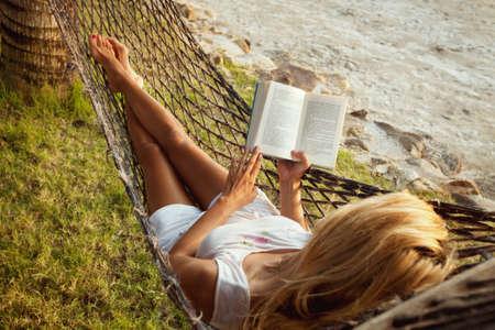 personas leyendo: Mujer acostada en una hamaca en la playa y disfrutar de un libro de lectura Foto de archivo