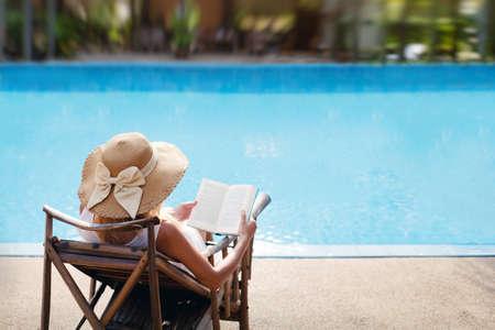 mujer leyendo libro: mujer que lee y relajantes cerca de la piscina de lujo