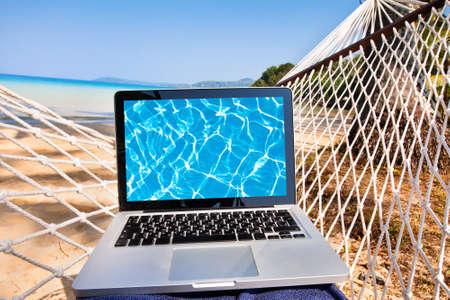 Laptop in hangmat op het strand