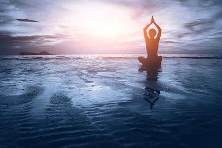 Pojęcie dobrego samopoczucia, piękny zachód słońca na plaży, kobieta uprawiania jogi