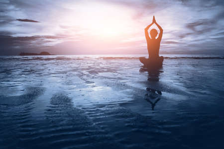 well being concept, beautiful sunset on the beach, woman practicing yoga 版權商用圖片 - 53075198