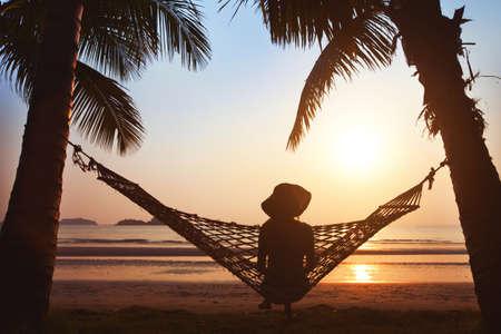 vacaciones en la playa: mujer que se relaja en hamaca al atardecer en la playa