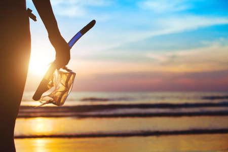 cielo y mar: aventura playa, silueta de la mano con el equipo para bucear