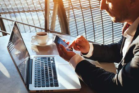medios de informaci�n: hombre de negocios usando Internet en el tel�fono inteligente y port�til
