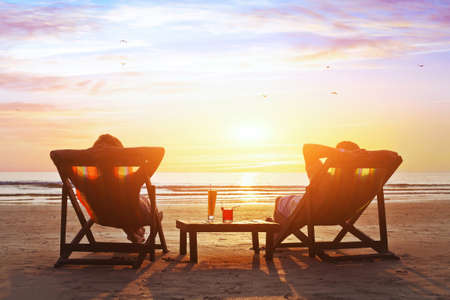 tourist resort: happy couple enjoy luxury sunset on the beach during summer vacations
