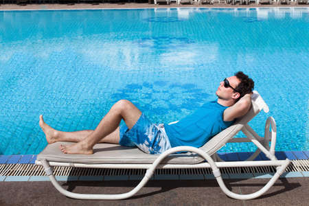 sucessful: young reach sucessful businessman relaxing near big luxury swimming pool