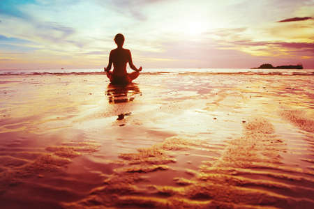 enlightenment, silhouette of woman practicing yoga on the beach