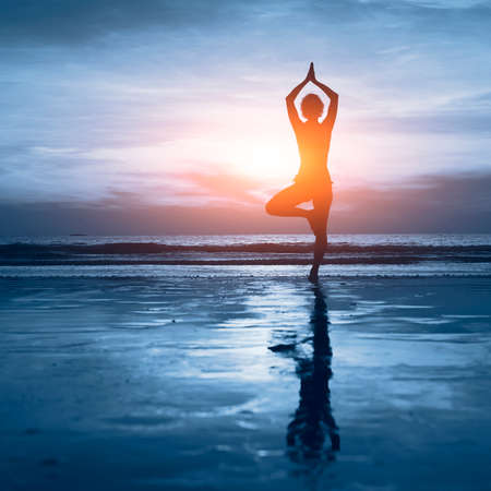 yoga sunset: wellness concept, beautiful silhouette of woman practicing yoga Stock Photo