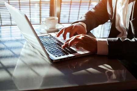 mecanografía: trabajando en la computadora portátil, cerca de las manos del hombre de negocios