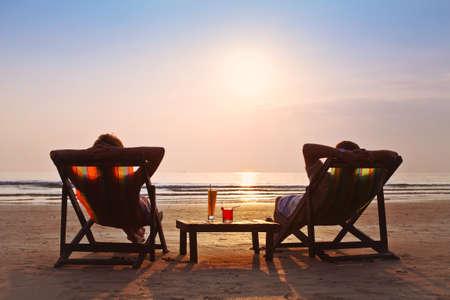 幸せなカップルは、ビーチで夕日を楽しむ