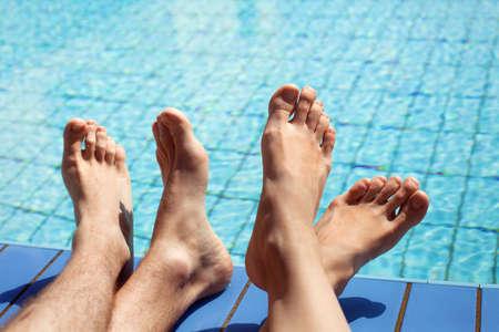 swimming pool woman: feet of couple near swimming pool