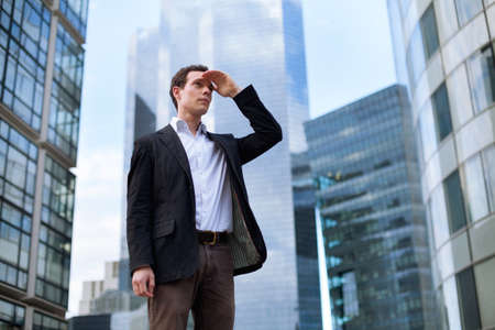 one person: young business man looking forward on skyscrapers background