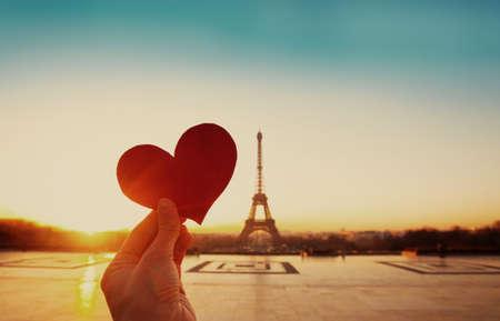 schreiben: Schöne alte Karte von Paris, Eiffelturm und die Hand mit Papier-Herz bei Sonnenaufgang