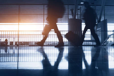 overseas: abstract airport background with walking commuters