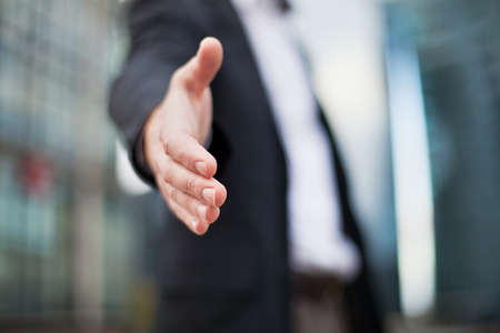 stretta di mano: Uomo d'affari che offre per la stretta di mano su edifici per uffici di sfondo