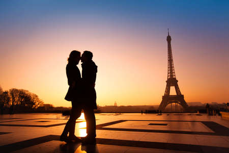 paris at night: loving couple kissing on Eiffel Tower background, Paris, France