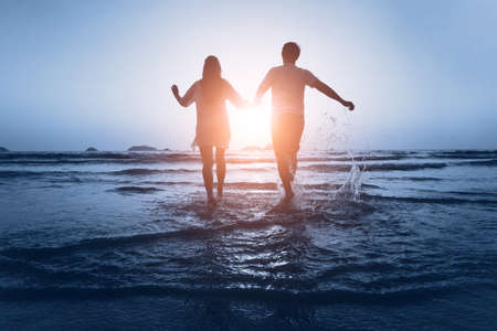woman sunset: loving couple enjoy the sea at sunset