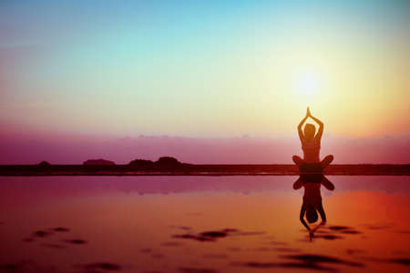 spirit: Silhouette of young woman practicing yoga on the beach at sunset Stock Photo