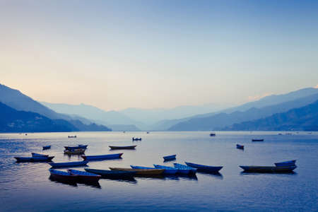 still water: scenic panoramic view of boat on the lake by sunset, Nepal, Pokhara Stock Photo
