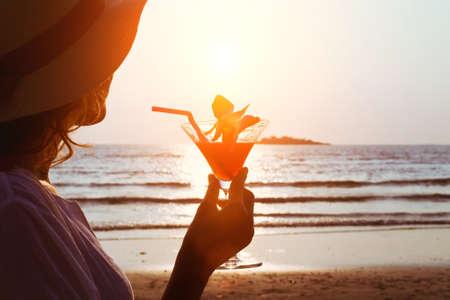 jovenes tomando alcohol: Mujer con el coctel en la playa Foto de archivo