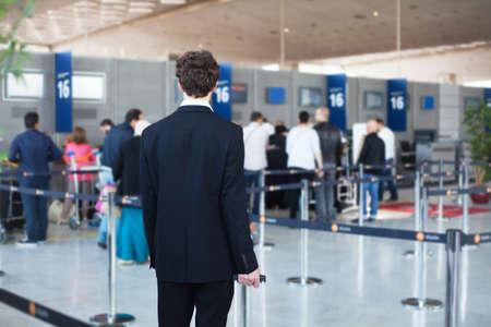 空港でチェックインし、荷物を降ろすキューで待っている乗客の人々 写真素材