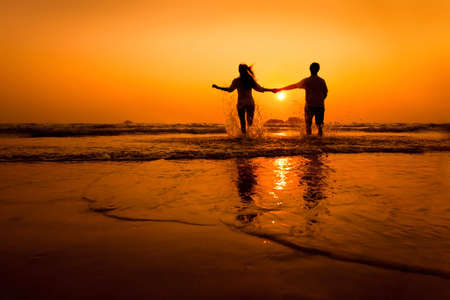 woman relax: silhouettes of couple running to the sea on the beach at sunset Stock Photo