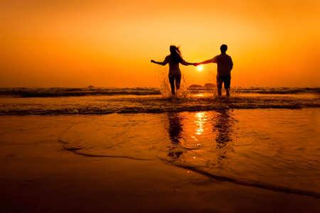 Siluetas de los pares se ejecutan al mar en la playa al atardecer