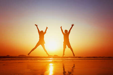 wellness woman: happy couple jumping on  the beach