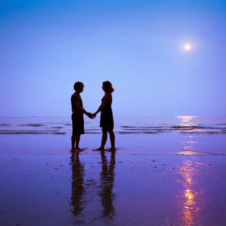 romantic date: romantic date, silhouettes of loving couple on the beach Stock Photo