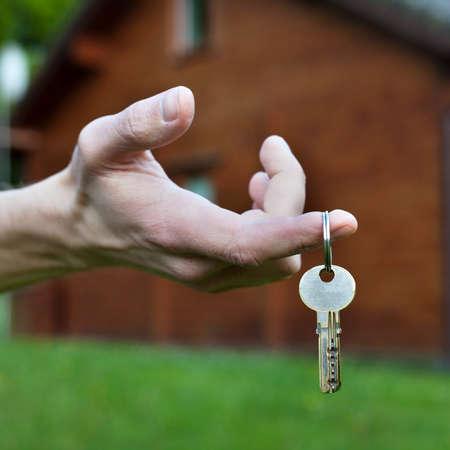 garden key: buy cottage, real estate concept, keys in the hand